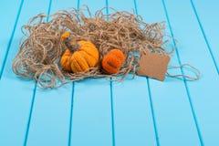 Домодельные тыквы, шпагат и карточка хеллоуина на голубой деревянной предпосылке Стоковое Изображение RF