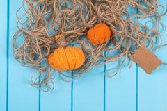 Домодельные тыквы, шпагат и карточка хеллоуина на голубой деревянной предпосылке Стоковые Фото