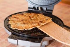 Домодельные waffles в утюге waffle с деревянным шпателем Стоковая Фотография