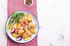 Домодельный вкусный зажаренный в духовке цыпленк цыпленок подгоняет с зажаренной в духовке картошкой с овощами в шаре эмали Стоковые Фотографии RF