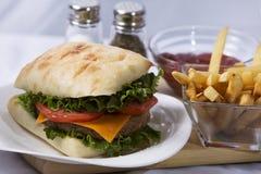 Домодельный здоровый Cheeseburger на плюшке Ciabatta, с французскими фраями Стоковое Изображение RF