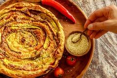 Домодельный круглый vegetable пирог служил с томатами вишни, перцем chili и семенами сезама в баке, женской руке держа деревянную Стоковая Фотография