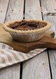 Домодельный малый круглый пирог с орехами карамельки служил с винтажной вилкой на деревянной предпосылке стоковое фото
