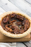Домодельный малый круглый пирог с орехами карамельки служил с винтажной вилкой на деревянной предпосылке Плоское положение стоковое фото