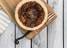 Домодельный малый круглый пирог с орехами карамельки служил с винтажной вилкой на деревянной предпосылке Плоское положение стоковая фотография