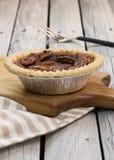 Домодельный малый круглый пирог с орехами карамельки служил с винтажной вилкой на деревянной предпосылке Плоское положение стоковое фото rf