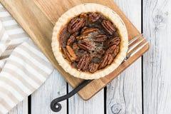 Домодельный малый круглый пирог с орехами карамельки служил с винтажной вилкой на деревянной предпосылке Плоское положение стоковые фото