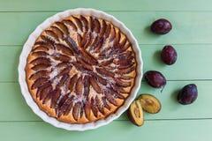Домодельный пирог сливы в керамическом блюде над голубым тонизированным взглядом инструментов Стоковая Фотография RF
