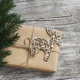 Домодельный подарок рождества в бумаге kraft, деревянном орнаменте оленей рождества, ветвях рождественской елки на деревенской св Стоковое Фото