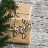 Домодельный подарок рождества в бумаге kraft, деревянном орнаменте оленей рождества, ветвях рождественской елки на деревенской св Стоковые Изображения