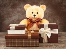 Домодельный плюшевый медвежонок и много коробки с подарками на старой доске Стоковое Фото