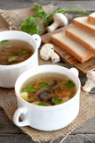 Домодельный суп гриба в шаре, куски хлеба на прерывая доске, свежие грибы и зеленая петрушка на деревянном столе Стоковое фото RF