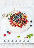 Домодельный торт Pavlova с свежими ягодами сада и серебряными ложками на белом подносе выпечки над светлой деревянной предпосылко стоковое фото
