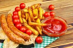 Домодельный фаст-фуд, часть фраев француза, кетчуп, зажарил сосиски и томат вишни на деревянной доске Стоковые Изображения RF