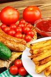 Домодельный фаст-фуд, часть фраев француза, кетчуп, зажарил сосиски и томат вишни на деревянной доске Стоковая Фотография RF