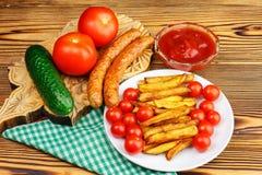 Домодельный фаст-фуд, часть фраев француза, кетчуп, зажарил сосиски и томат вишни на деревянной доске Стоковое Фото