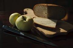 Домодельный хлеб, 2 яблока и нож на таблице Стоковые Фотографии RF