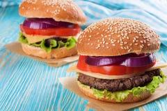 Домодельный cheeseburger на голубой деревянной поверхности Стоковое Фото