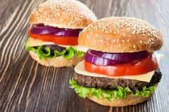 Домодельный cheeseburger на коричневой деревянной поверхности Стоковое Фото