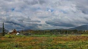 Дом в деревне с спутниковой антенна-тарелкой и загон для скотин в долине покрытой с травой на фоне холмов и пре--t Стоковое Изображение