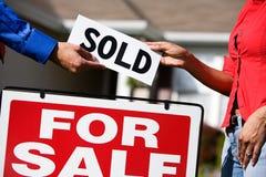 Дом: Дающ новому домовладельцу проданный знак стоковые фото