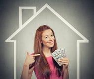 Дом, деньги, концепция людей Успешная бизнес-леди держа деньги наличных денег доллара стоковая фотография rf
