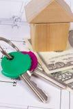 Дом деревянных блоков, ключей и доллара на чертеже конструкции, концепции валют дома здания Стоковая Фотография