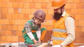 Дом здания отца и сына совместно r Мальчик малыша в оранжевом шлеме или шлеме помогает его бородатому видеоматериал