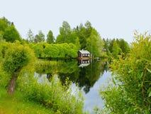 Дом и мост к озеру между деревьями стоковые изображения rf