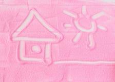 Дом и солнце на предпосылке декоративного песка стоковые изображения