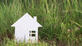 Дом картона сделанный из бумаги на предпосылке зеленой травы сток-видео