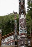 Дом клана Тлинкита с тотемными столбами в Ketchikan, Аляске стоковые изображения