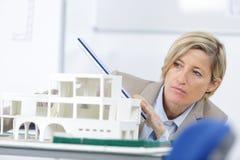 Дом масштабной модели и женская женщина архитектора в предпосылке Стоковые Фотографии RF