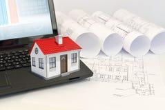Дом маленькой модели с красной крышей на компьтер-книжке близко Стоковое Изображение RF