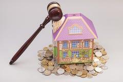 Дом, монетки и молоток имущество принципиальной схемы реальное Стоковые Изображения