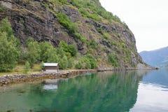 Дом на береге фьорда на ноге горы Стоковое фото RF