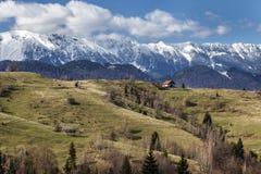 Дом на верхней части холма, снежная предпосылка горы, Стоковая Фотография