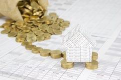 Дом на золотых монетках имеет переполнение денег нерезкости от мешка Стоковое Фото