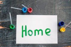 Дом надписи покрасил зеленую краску на белой бумаге дом дома принципиальной схемы предпосылки изолированная над белизной стоковая фотография