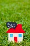 Дом - домашний - покупка или надувательство - на траве Стоковое Фото