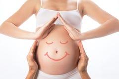 Дом от рук вокруг беременного живота стоковые фото