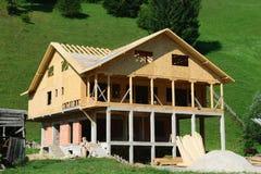 Дом под конструкцией и зелеными холмами на заднем плане Стоковые Изображения RF