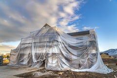 Дом под конструкцией покрытой с пластмассой против горы и облачного неба стоковые фотографии rf
