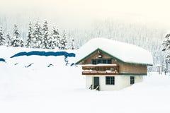 Дом покрытый с толстым снегом на крыше с предпосылкой леса снега Стоковое Изображение
