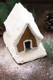 Дом пряника Snowy с снежинками рождественской елкой и глобусом на предпосылке каменной стены Домодельные печенья рождества - ging Стоковые Изображения RF