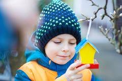 Дом птицы смертной казни через повешение маленького ребенка на дереве для подавать в зиме Стоковое Изображение RF