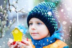 Дом птицы смертной казни через повешение маленького ребенка на дереве для подавать в зиме Стоковые Фотографии RF