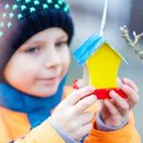 Дом птицы смертной казни через повешение маленького ребенка на дереве для подавать в зиме Стоковые Изображения