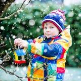 Дом птицы смертной казни через повешение мальчика маленького ребенка на дереве для подавать в зиме Стоковые Изображения RF