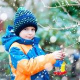 Дом птицы смертной казни через повешение мальчика маленького ребенка на дереве для подавать в зиме Стоковое фото RF